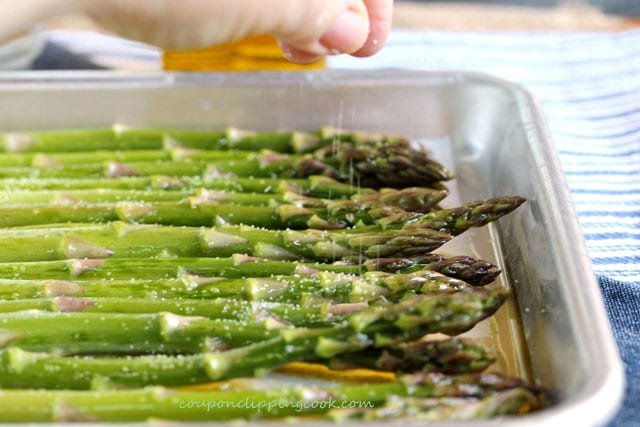 Add salt on asparagus on baking pan