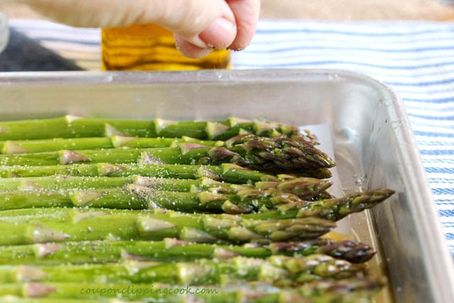 Add pepper on asparagus on baking pan