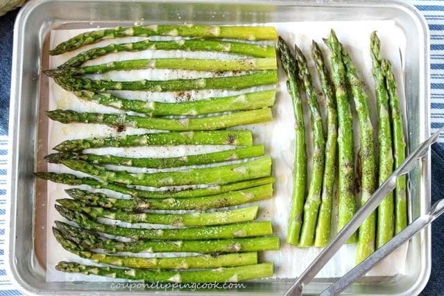 Seasoned asparagus on baking pan with tongs