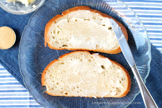 Spread butter on slices of bread on plate