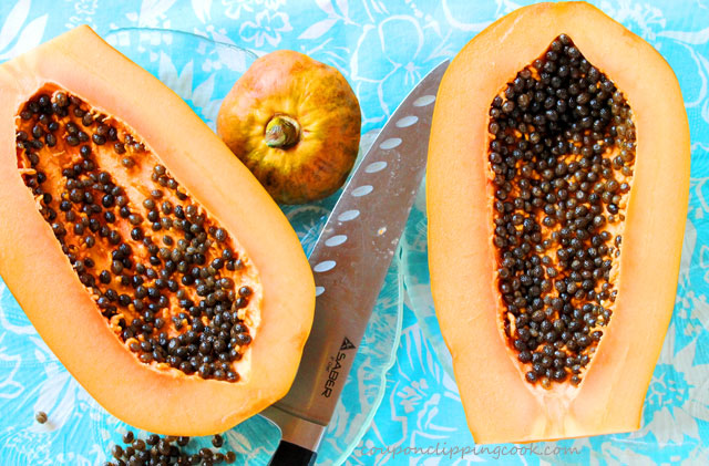 Cut Mexican papaya in half with knife