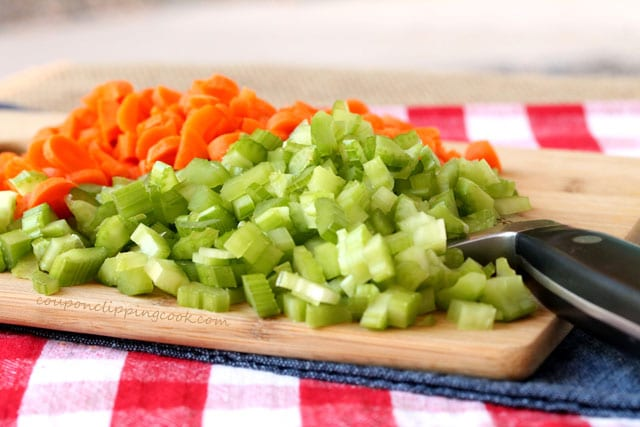 Chopped celery and carrots on cutting board with knife