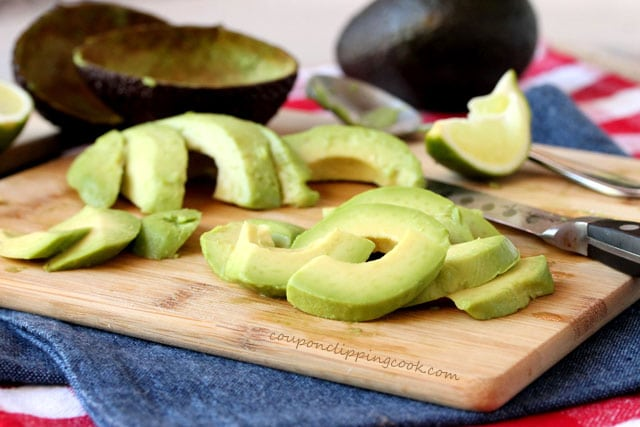 Sliced avocado on cutting board with knife