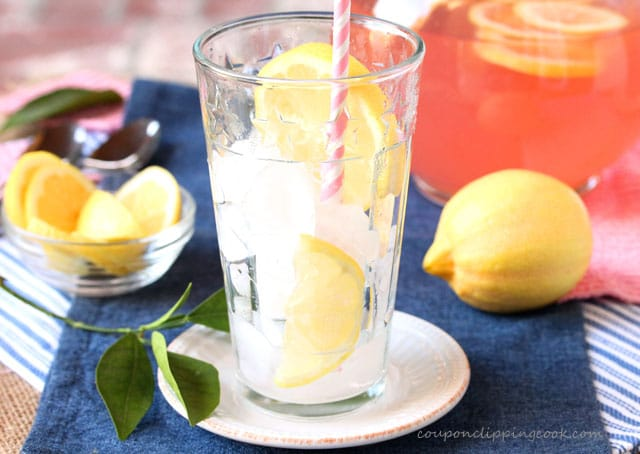Emply glass of pink lemonade with sliced lemon and straw