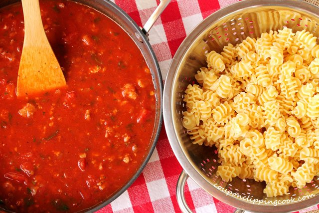 Marinara sauce in pot with pasta in colander