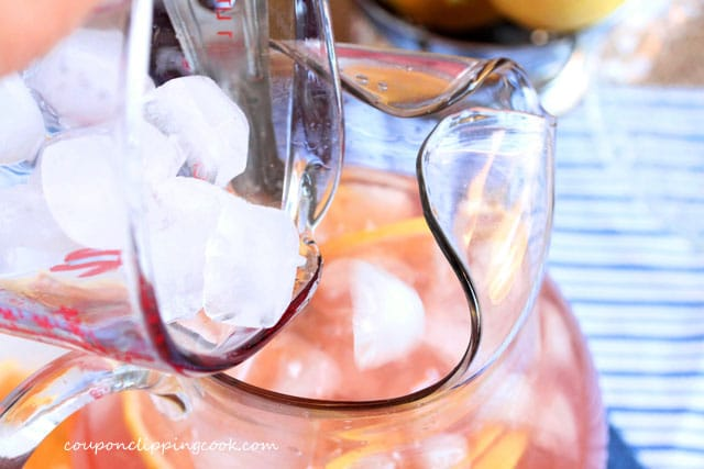 Add ice cubes to pink lemonade in pitcher