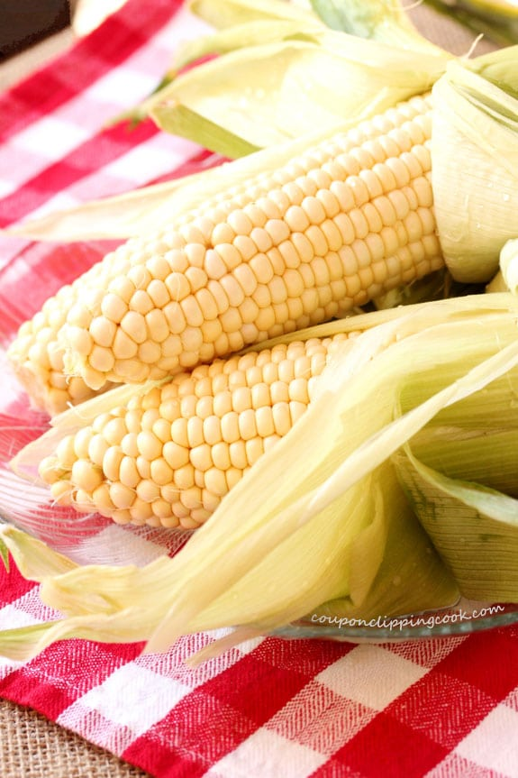 Ears of corn with husks pulled back on plate