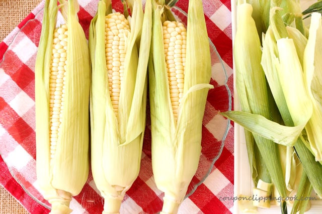 Ears on corn with husks pulled back on plate