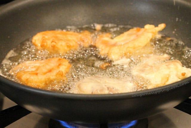 Fry battered shrimp in skillet with oil