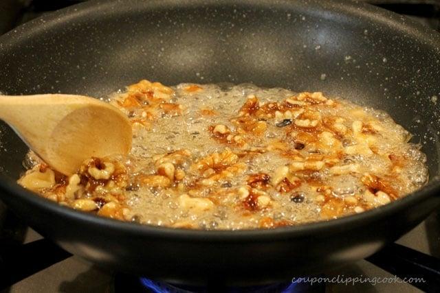 Stir candied walnuts in skillet