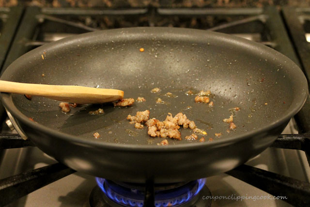 Skillet on stove top with bits of sausage