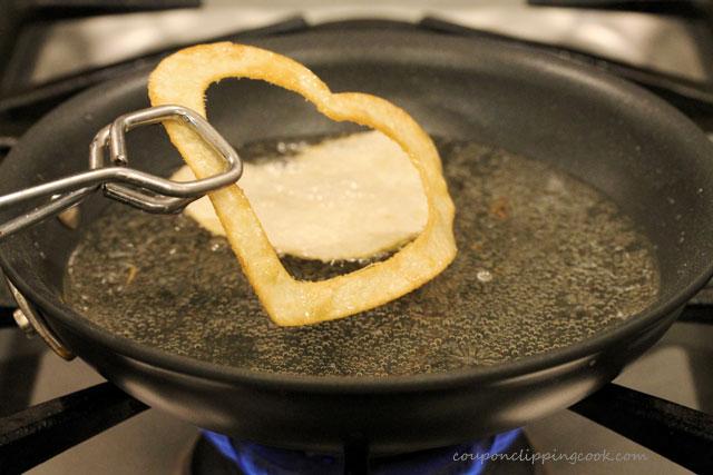 Fry heart shaped tortilla chips in pan