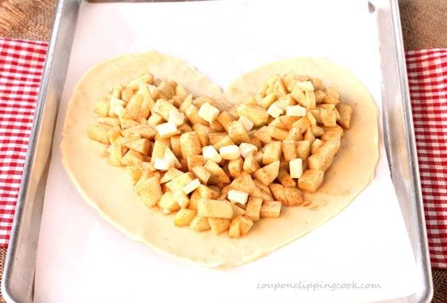 Apple pie filling on heart shaped dough