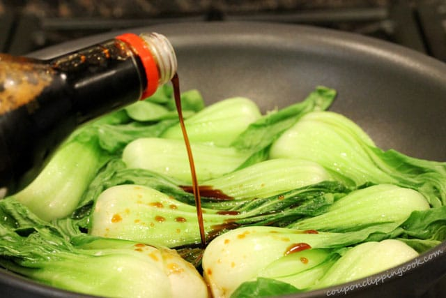 Pour soy sauce on baby bok choy in pan