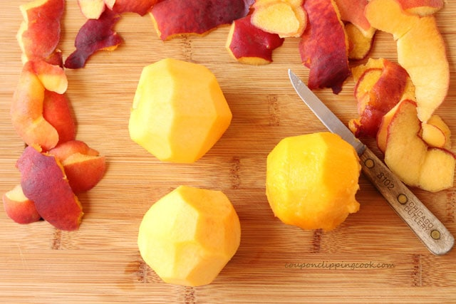 Peeled peaches on cutting board