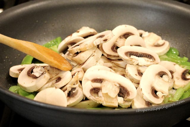 Stir mushrooms in pan