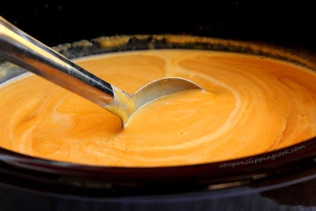 Stir squash soup in pot
