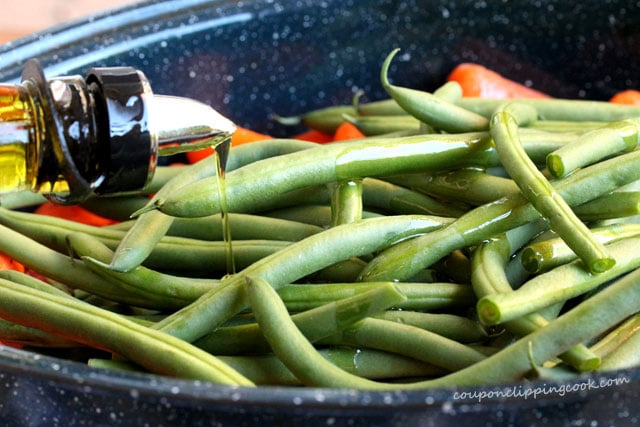 Olive oil on green beans in pan