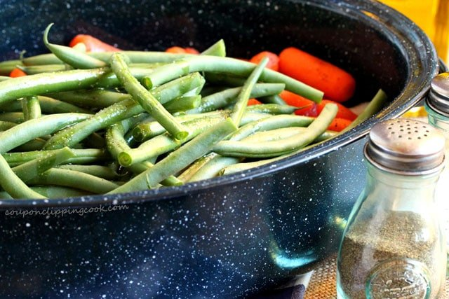 Salt pepper on green beans in pan