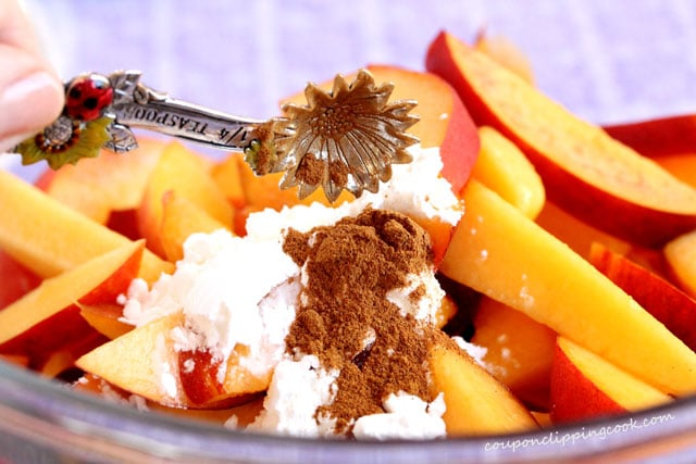 Add cinnamon to peaches in bowl