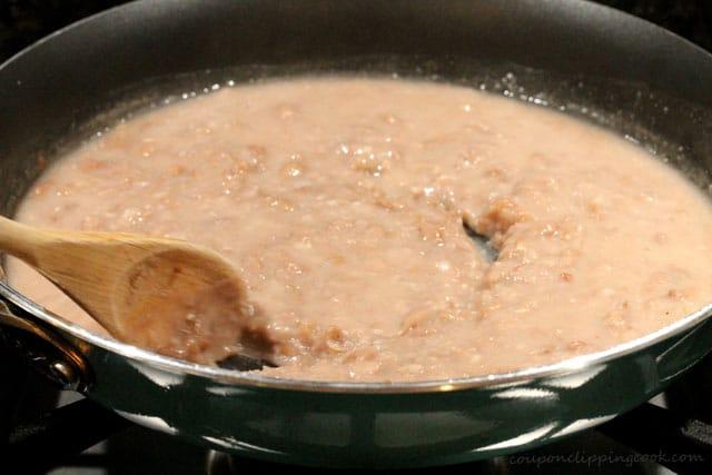 Stir refried beans in pan