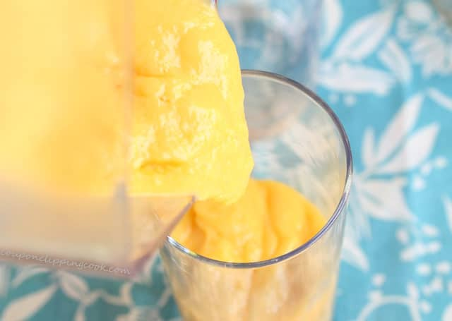 Pour mango smoothie in glass