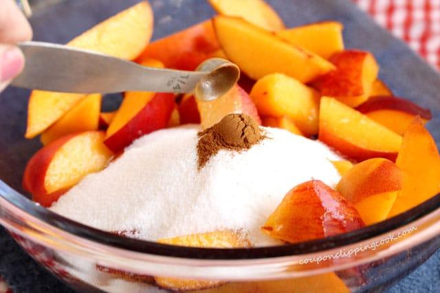Add cinnamon on sliced peaches